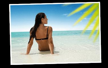 Frau im Bikini am Strand mit Palmen